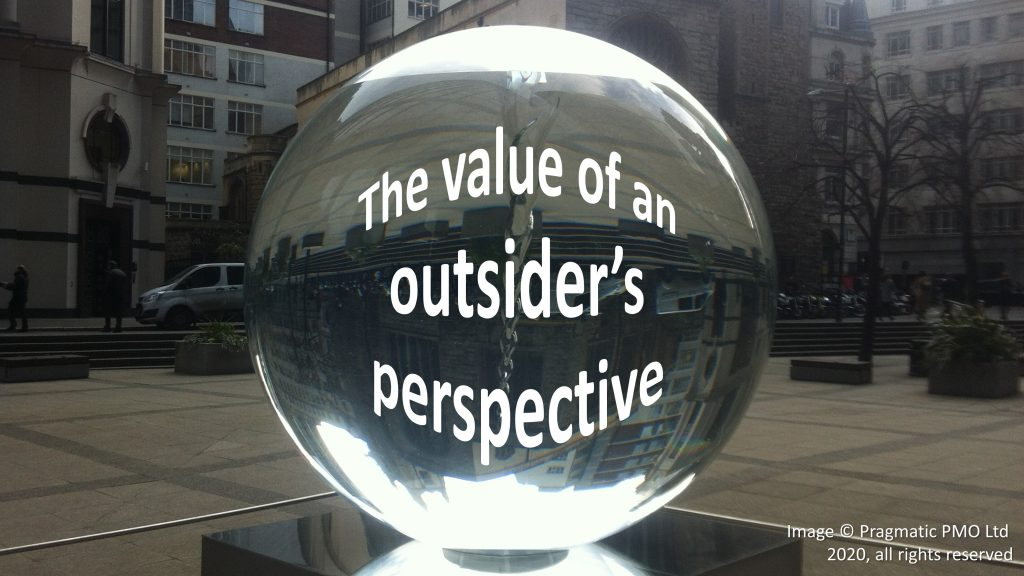 "Photograph of a large water-filled acrylic sphere sculpture outdoors. Distorted by the sphere is the caption ""The value of an outsider's perspective"""